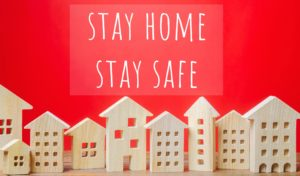 "small wood houses with a banner that says ""stay home stay safe"""