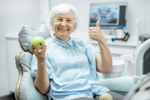 Smiling woman with dental implants in Pasadena holding an apple