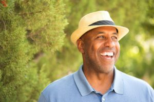 man in blue polo and fedora smiling with dental implants