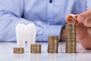 Model tooth next to increasing stacks of coins from dental insurance